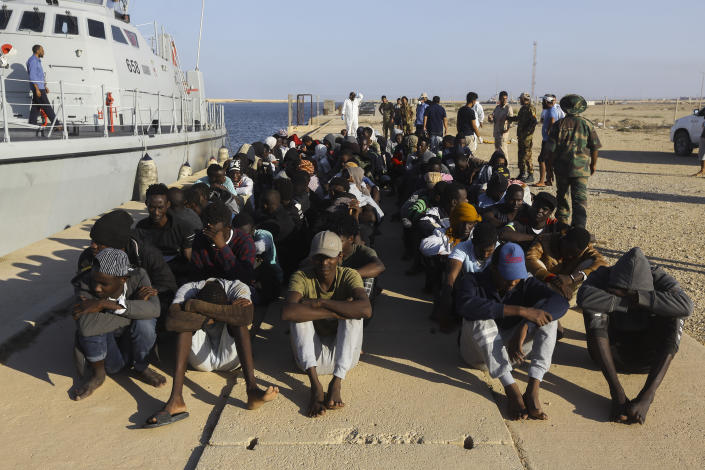 Rescued migrants are seated next to a coast guard boat in the city of Khoms, around 120 kilometers (75 miles) east of Tripoli, Libya, Tuesday, Oct. 1, 2019. (AP Photo/Hazem Ahmed)