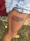A race fan with a NASCAR tattoo is shown in the infield at the Daytona International Speedway before a truck race Friday, Feb. 12, 2021, in Daytona Beach, Fla. Daytona is used to shirtless fans partying in the infield. But what about maskless ones? Usually the biggest NASCAR party of the season, the sport will have to figure out how to police up to 30,000 fans who may have little interest in sticking to the pandemic guidelines. How many fans will actually come remains to be seen.(AP Photo/Daniel Gelston)