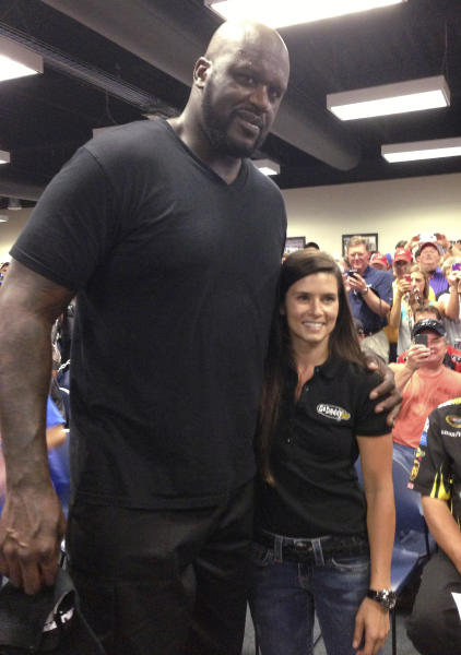 Former NBA star Shaquille O'Neal, left, and Danica Patrick pose for photos at the drivers' meeting prior to the NASCAR Sprint Cup auto race at Daytona International Speedway, Saturday, July 6, 2013, in Daytona Beach, Fla. (AP Photo/Jenna Fryer)