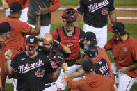 Washington Nationals catcher Kurt Suzuki, center top, and teammates celebrate after the second baseball game of a doubleheader against the New York Mets, Saturday, Sept. 26, 2020, in Washington. (AP Photo/Nick Wass)