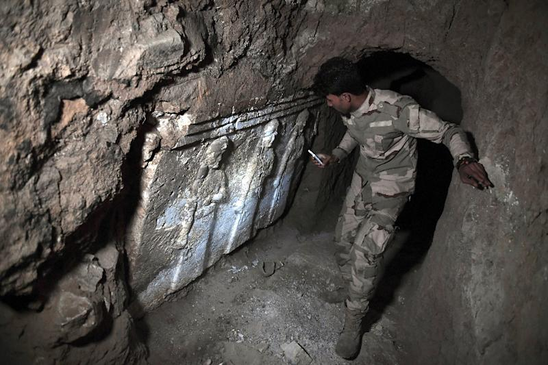 A member of the Iraqi troops stands next to archeological findings inside an underground tunnel in east Mosul, northern Iraq on March 6, 2017 (AFP Photo/ARIS MESSINIS)
