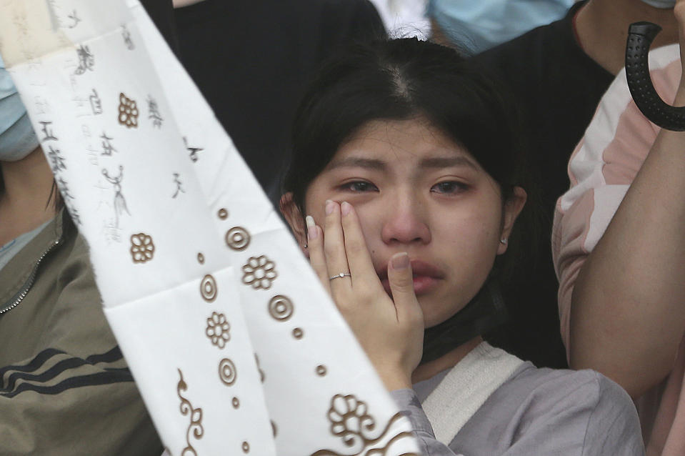 The families of the victims in a train crash cry as they mourn near Taroko Gorge in Hualien, Taiwan on Saturday, April 3, 2021. The train partially derailed in eastern Taiwan on Friday after colliding with an unmanned vehicle that had rolled down a hill, killing and injuring dozens. (AP Photo/Chiang Ying-ying)