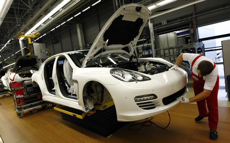 A worker works on a Panamera car at the final production unit at the Porsche plant in Leipzig