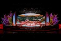 Performers take part in a cultural performance with an image of the Great Wall seen in the background in Macau