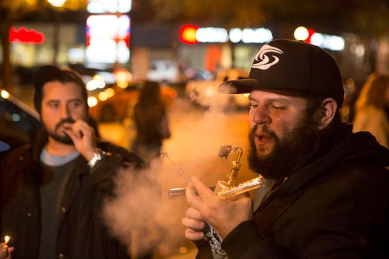 People smoke cannabis on the street in Toronto after the drug was legalised at midnight (Chris Young/AP)