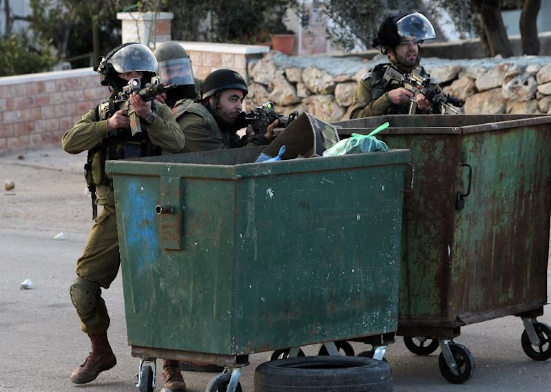 Israeli security forces position themselves behind trash bins during clashes with Palestinian demonstrators following a protest against the expansion of settlements on March 20, 2015, in the West Bank village of Silwad, north of Ramallah (AFP Photo/Abbas Momani)