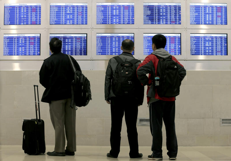 In this Monday, Oct. 29, 2012, photo, travelers on Delta Airlines look at a departure screen, in Detroit. Major airlines scrapped flights in and out of the New York area Wednesday, Nov. 7, 2012, as the region gets socked with the second significant storm in little more than a week.  (AP Photo/Charlie Riedel)