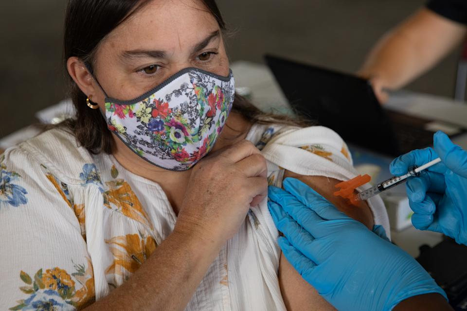 SOUTHFIELD, MI - AUGUST 24: A patient receives her booster dose of the Pfizer-BioNTech coronavirus (COVID-19) vaccine during an Oakland County Health Department vaccination clinic at the Southfield Pavilion on August 24, 2021 in Southfield, Michigan. Oakland County is the second county in Michigan to reach the state's goal of vaccinating 70% of its population. (Photo by Emily Elconin/Getty Images)