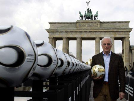 Franz Beckenbauer, President of Germany's World Cup organising committee, holds a golden soccer ball during a presentation next to the Brandenburg gate in Berlin April 18, 2006. REUTERS/Tobias Schwarz/File Photo