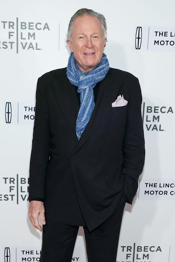 A man in a dark suit and blue scarf stands in front of a Tribeca Film Festival backdrop.