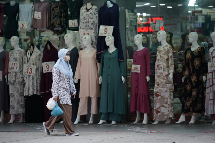 In this Friday, April 19, 2021, photo, a woman wearing a protective mask passes a clothing shop in the Ramadan bazaar in Kuala Lumpur, Malaysia. Malaysian Prime Minister Muhyiddin Yassin announced Monday that the whole country will be placed under a near lockdown for about a month but all economic sectors will be allowed to operate. (AP Photo/Vincent Thian)