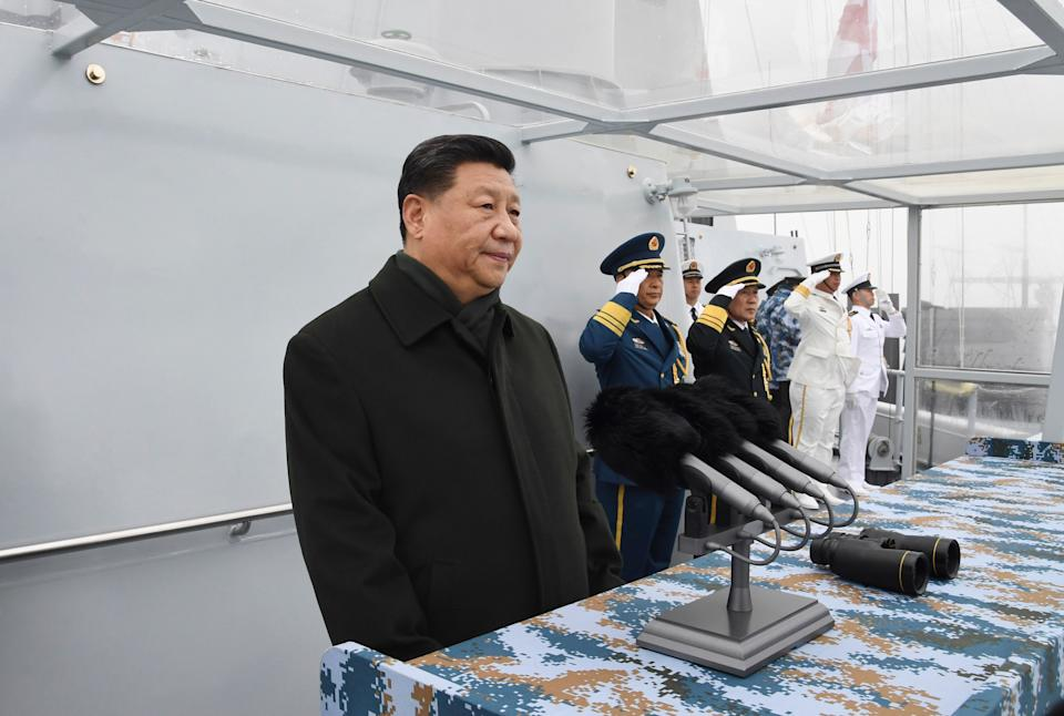 Chinese President Xi Jinping reviews a naval parade with Chinese and foreign military ships held in commemoration of the 70th anniversary of the Chinese People's Liberation Army (PLA) Navy in the sea near Qingdao in eastern China's Shandong Province, Tuesday, April 23, 2019. (Li Gang/Xinhua via AP)