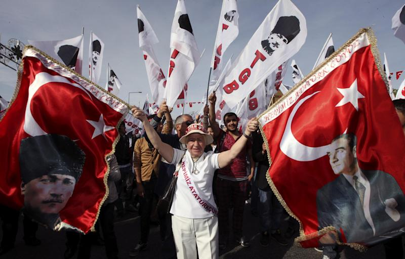 A woman holds up national flags bearing depictions of Turkey's founder Kemal Ataturk prior to a march to the mausoleum of Ataturk to celebrate the Republic Day in Ankara, Turkey, Monday, Oct. 29, 2012. Police on Monday used tear gas and water cannons to try to break up a demonstration by tens of thousands of pro-secular protesters, but the march to mark the founding of the Turkish republic went on in defiance of a government ban. (AP Photo/Burhan Ozbilici)