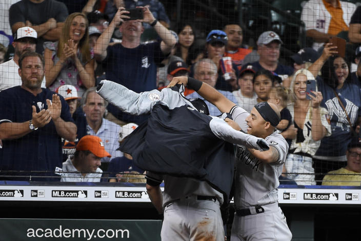 New York Yankees' Rougned Odor, right, puts a jacket on Gary Sanchez after Sanchez's three-run home run during the eighth inning of a baseball game against the Houston Astros, Sunday, July 11, 2021, in Houston. (AP Photo/Eric Christian Smith)