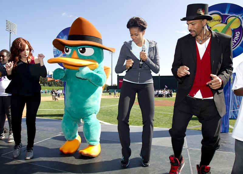 First lady Michelle Obama dances the platypus dance with Disney actress Debby Ryan, left, Perry the Platypus of the Phineas and Ferb show, second from left, and choreographer Rosero McCoy, right, at the ESPN Wide World of Sports Complex at the Walt Disney World Resort, Saturday, Feb. 11, 2012, in Orlando, Fla., during her three day national tour celebrating the second anniversary of Let's Move. (AP Photo/Carolyn Kaster)