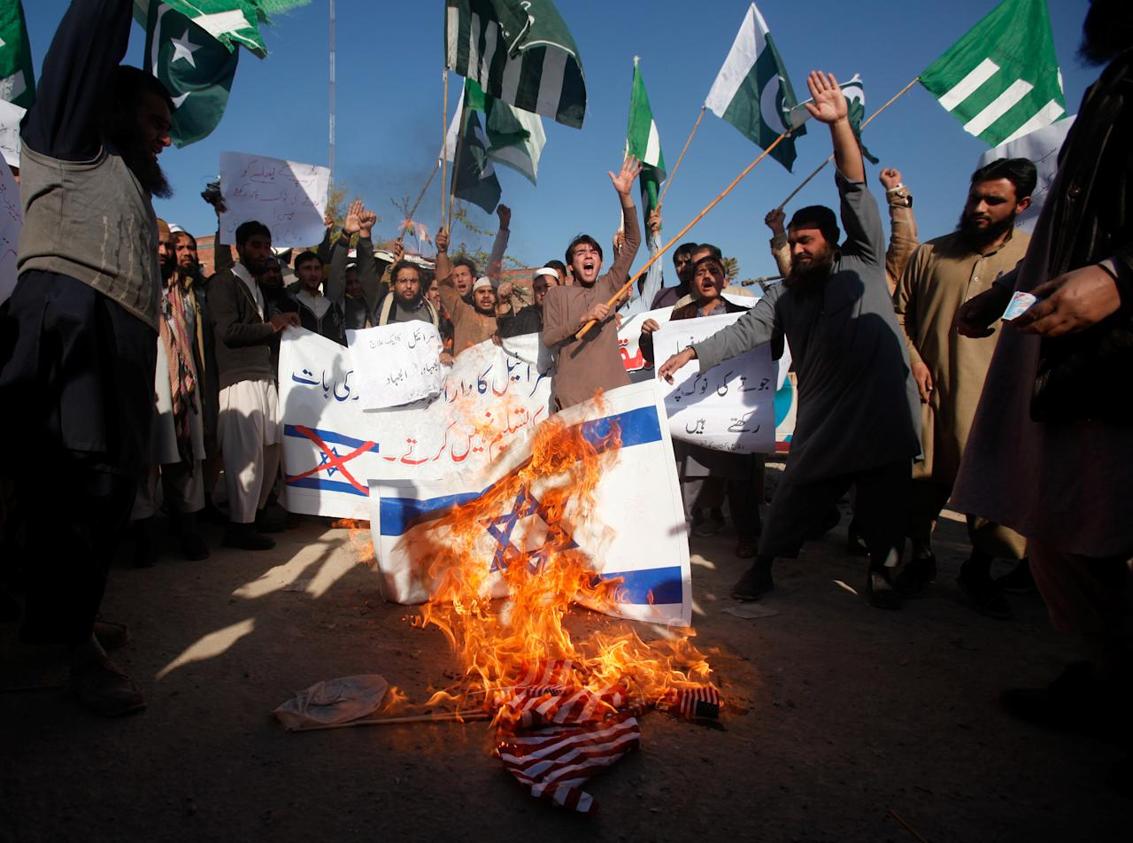 <p>Supporters of the Difa-e-Pakistan Council (DPC), an Islamic organization, chant slogans as they burn Israeli and U.S. flags during a protest against President Donald Trump's decision to recognize Jerusalem as the capital of Israel, in Peshawar, Pakistan, Dec. 7, 2017. (Photo: Fayaz Aziz/Reuters) </p>