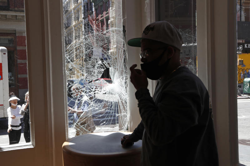 A glass installer adjusts his face protection mask before installing plywood over the broken windows of a Bang and Olafson store, Sunday, May 31, 2020, in the trendy SoHo neighborhood of New York, which was vandalized during protests over the death of George Floyd Saturday night. Floyd died Memorial Day in Minneapolis while in police custody. (AP Photo/Kathy Willens)