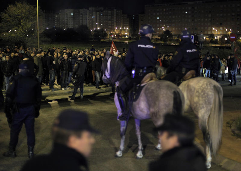 Protestors try to stop buses to run as the police stand guard outside a main bus garage during a general strike in Madrid, Spain, Wednesday, Nov. 14, 2012. Spain's main trade unions stage a general strike, coinciding with similar work stoppages in Portugal and Greece, to protest government-imposed austerity measures and labor reforms. The strike is the second in Spain this year. (AP Photo/Andres Kudacki)