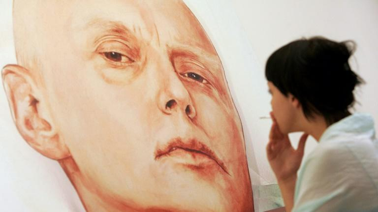 A visitor looks at a painting showing former Russian spy Alexander Litvinenko in his hosital bed in London by artists Dmitry Vrubel and Viktoria Timofeyeva