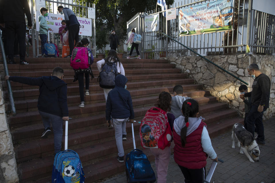 FILE - In this Feb. 11, 2021, file photo, Israeli pupils arrive to school in the central Israeli city of Herzliya. While Israel provides a glimpse of what may be possible with high immunization rates, it also offers insight into the problems that lie ahead: Workplaces and schools are now grappling with what to do with those who refuse to get vaccinated. (AP Photo/Sebastian Scheiner, File)
