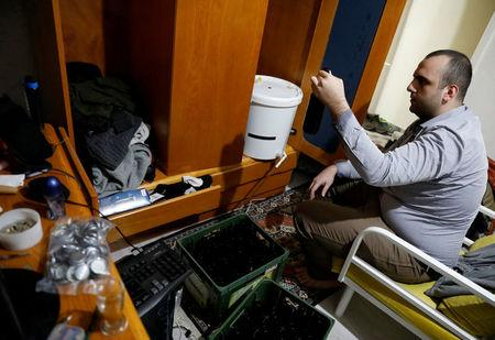 Onder Ceyhan, a 25-year old university student, checks a bottle as he brews his own beer at his home in Ankara, Turkey, November 6, 2017. REUTERS/Umit Bektas