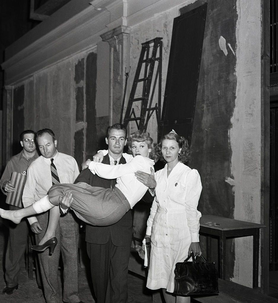 <p>While filming a scene for <em>Dark Corners</em>, Lucille tripped and fell from the stage. After injuring herself, she was carried off of the set by her costar Mark Stevens, while a doctor and nurse look on. </p>