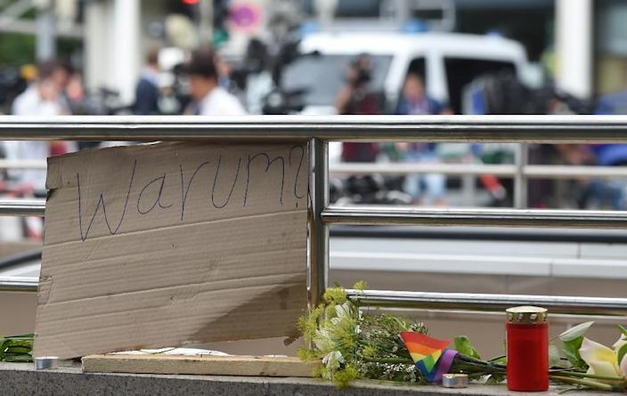 """A sign reading """"Why?"""" next to candles and flowers at an underground station near the Olympia-Einkaufszentrum shopping centre on July 23, 2016, one day after the attack in Munich (AFP Photo/Christof Stache)"""