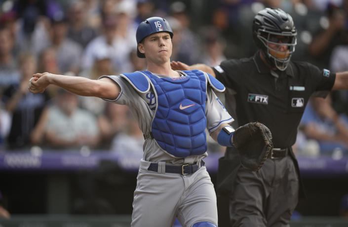 Los Angeles Dodgers catcher Will Smith throws to first base to put out Colorado Rockies' Brendan Rodgers in the ninth inning of a baseball game Thursday, Sept. 23, 2021, in Denver. (AP Photo/David Zalubowski)