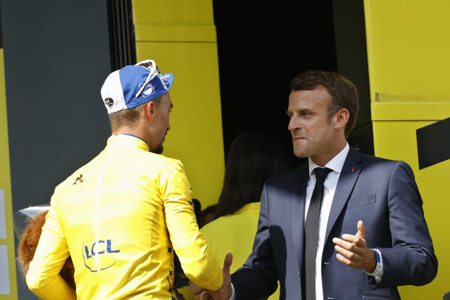 France's Julian Alaphilippe wearing the overall leader's yellow jersey is congratulated by France's President Emmanuel Macron on the podium after the fourteenth stage of the Tour de France cycling race over 117.5 kilometers (73 miles) with start in Tarbes and finish at the Tourmalet pass, France, Saturday, July 20, 2019. (AP Photo/ Christophe Ena)