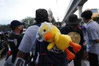 A protester's backpack is adorned with a large yellow duck, which has become a good-humored symbol of resistance during anti-government rallies, while waiting for other protesters outside the base entrance of the 11th Infantry Regiment, a palace security unit under direct command of the Thai king, Sunday, Nov. 29, 2020, in Bangkok, Thailand. Pro-democracy demonstrators are continuing their protests calling for the government to step down and reforms to the constitution and the monarchy, despite legal charges being filed against them and the possibility of violence from their opponents or a military crackdown. (AP Photo/Sakchai Lalit)
