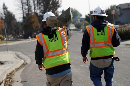 FILE PHOTO: Pacific Gas and Electric (PG&E) workers walk during a gas line inspection in a neighborhood destroyed by the Tubbs Fire, in Santa Rosa