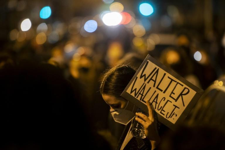 """A demonstrator, wearing a protective face mask, holds a placard reading """"WALTER WALLACE JR."""" during a protest near the location where Walter Wallace, Jr. was killed by two police officers"""