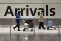 Arriving passengers walk past a sign in the arrivals area at Heathrow Airport in London, Tuesday, Jan. 26, 2021, during England's third national lockdown since the coronavirus outbreak began. The British government are on Tuesday expected to discuss whether to force some travellers arriving in the UK to quarantine in hotels to try to curb the spread of coronavirus. (AP Photo/Matt Dunham)