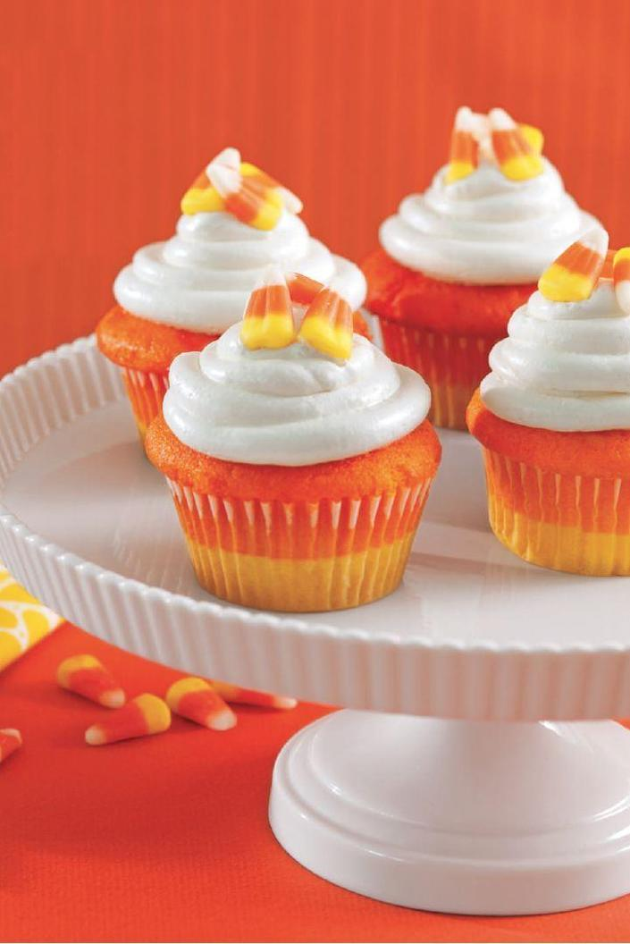 """<p>To get this perfect gradient of color, top yellow-colored batter with orange batter and then decorate with white frosting. </p><p><em><strong><a href=""""https://www.womansday.com/food-recipes/food-drinks/a28835151/candy-corn-cupcakes-recipe/"""" rel=""""nofollow noopener"""" target=""""_blank"""" data-ylk=""""slk:Get the Candy Corn Cupcakes recipe."""" class=""""link rapid-noclick-resp"""">Get the Candy Corn Cupcakes recipe.</a></strong></em></p>"""
