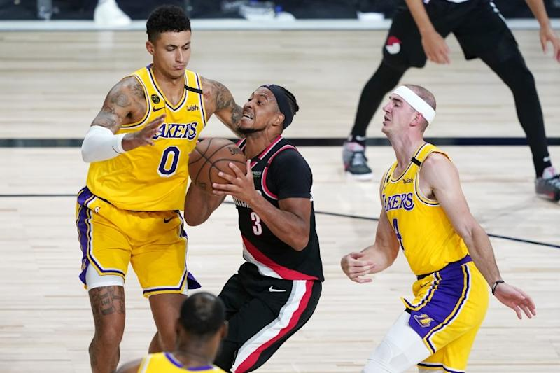 The Trail Blazers' CJ McCollum drives against the Lakers' Kyle Kuzma, left, and Alex Caruso on Aug. 29, 2020.