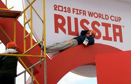 Workers rest while they put their final touches to a booth in Kazan Arena, ahead of the start of the World Cup Russia 2018 in Kazan, Russia June 14, 2018. REUTERS/Toru Hanai