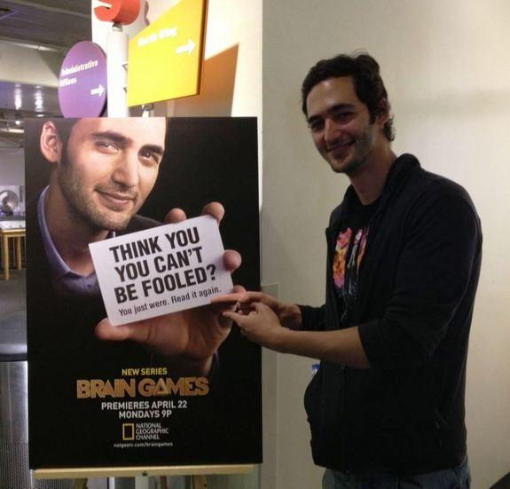 """Jason Silva, the host of National Geographic Channel's show """"Brain Games,"""" pointing to his poster. It may trick you."""