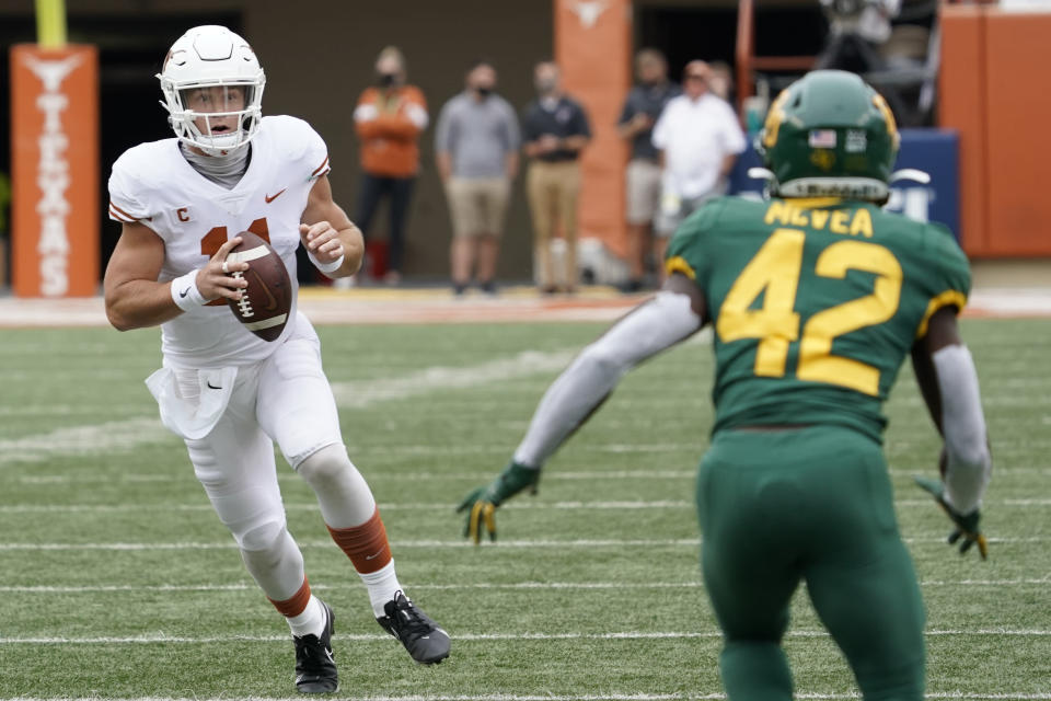 Texas' Sam Ehlinger (11) scrambles against Baylor's Jairon McVea (42) during the first half of an NCAA college football game in Austin, Texas, Saturday, Oct. 24, 2020. (AP Photo/Chuck Burton)