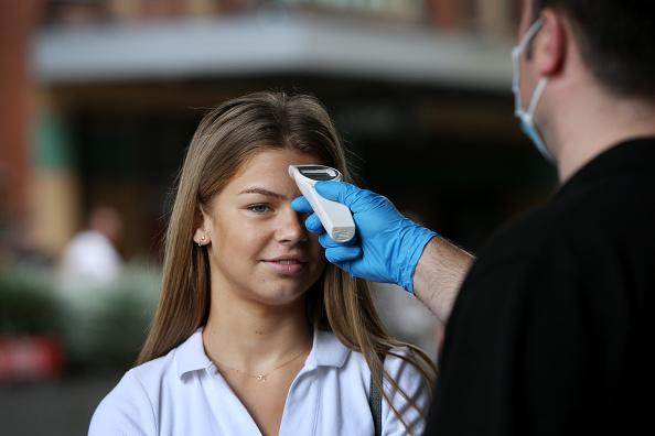 A customer has her temperature tested prior to entering the Apple Store at Sydney's Bondi Junction.