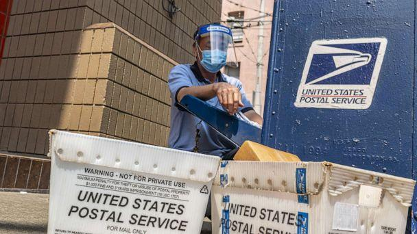 PHOTO: A U.S. Postal Service worker wearing a protective mask and face shield removes mail from a dropbox in San Francisco, Calif., Aug. 17, 2020. (David Paul Morris/Bloomberg via Getty Images)