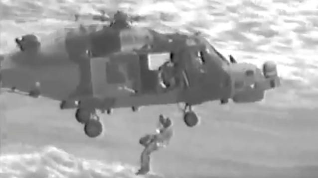 Helicopter crew members braved high winds and choppy seas to winch three members of a family to safety from a boat capsized by Hurricane Maria.