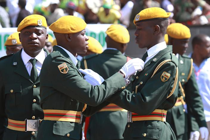 Zimbabwean soldiers adjust their ties at the country's Commemoration of Heroes day in Harare, Monday, Aug.12, 2013. Zimbabwean President elect Robert Mugabe received more than 60 percent of the vote in recent Presidential elections while his main challenger Morgan Tsvangirai is challenging the results in court and declaring the election null and void. (AP Photo/Tsvangirayi Mukwazhi)