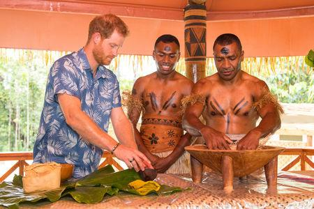 Britain's Prince Harry takes part in a demonstration of kava making by Joeli Nasqqa (centre) and Eparama Uluiuiti (right) at a dedication of the Colo-i-Suva forest to the Queen's Commonwealth Canopy in Suva, Fiji, October 24, 2018. Dominic Lipinski/Pool via REUTERS