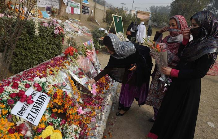 Pakistani mourners leave floral tributes outside the army-run school where 149 people were massacred by the Taliban, in Peshawar on December 21, 2014 (AFP Photo/A Majeed)