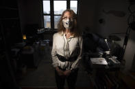 Bonney Ginett poses for a photo in her apartment in the Queens borough of New York on Thursday, March 18, 2021. Ginett, whose massage therapy business dried up during the pandemic, applied for help in July and said she was denied in October because she failed to prove loss of income. The 65-year-old New York City resident now owes more than $26,000 in back rent on her one-bedroom apartment and fears eviction. (AP Photo/Robert Bumsted)