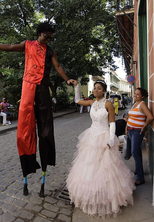 <p>A street entertainer greets Carmen Gonzalez (C), who walks with her mother Marlen (R), during a photo session in the old quarters of Havana as part of her quinceanera (coming-out for 15-year-olds) celebration.</p>