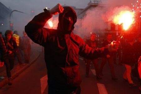 A far-right protester holds a flare during the annual far-right rally, which coincides with Poland's National Independence Day in Warsaw
