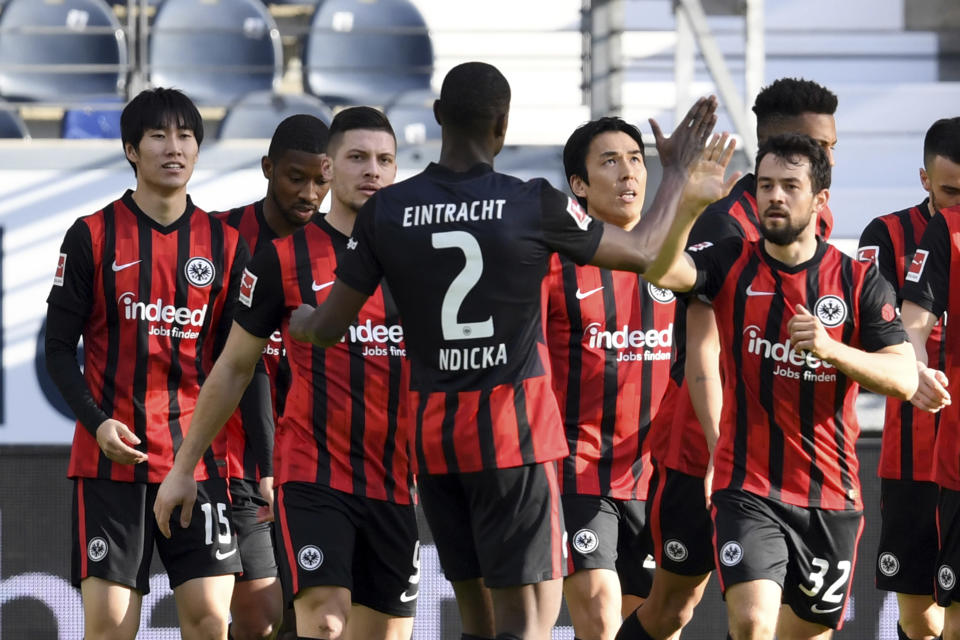 Frankfurt's Daichi Kamada, left, celebrates with team mates after he scores the opening goal during the German Bundesliga soccer match between Eintracht Frankfurt and Bayern Munich in Frankfurt, Germany, Saturday, Feb. 20, 2021. (Arne Dedert/POOL via AP)