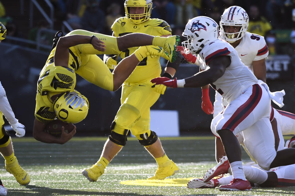 Oregon running back Travis Dye (26) is upended during a run in the second quarter of an NCAA college football game against Stony Brook Saturday, Sept. 18, 2021, in Eugene, Ore. (AP Photo/Andy Nelson)