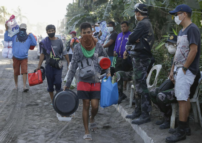 Men carry their belongings as authorities enforced total evacuation of residents living near the active Taal volcano in Agoncillo town, Batangas province, southern Philippines on Thursday Jan. 16, 2020. Taal volcano belched smaller plumes of ash Thursday but shuddered continuously with earthquakes and cracked roads in nearby towns, which were blockaded by police due to fears of a bigger eruption. (AP Photo/Aaron Favila)